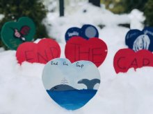 A close up of several paper hearts in the snow. From Queneesh Elementary School.